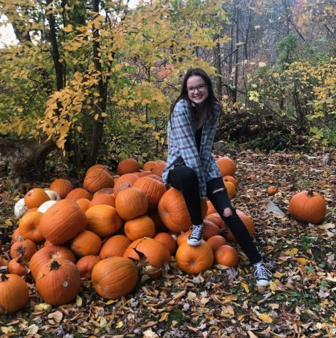 Shelby Anderson posing for a photo on a patch of pumpkins.