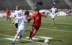 Battle for the ball. Senior Carson White(#19) fights a Smoky Hill defender for the ball.