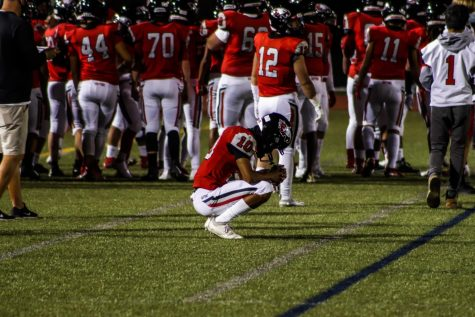 Week one, #10 Langston Williams (middle) crouches down on the sidelines while the team groups up to converse pregame.
