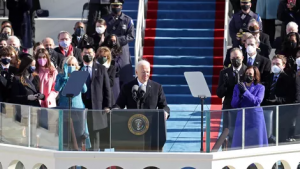 President Joe Biden during his Inaugural Address after being sworn in as 46th President of the United States, with members of the new administration and family members behind him. Image Courtesy of CNET.