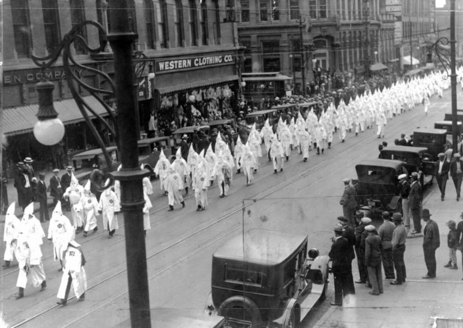 """Denver Post archive photo- Members of the Ku Klux Klan march in a parade on Larimer Street in Denver, May 31, 1926. They wear hoods and robes as spectators look on. Parked automobiles line the street."""""""