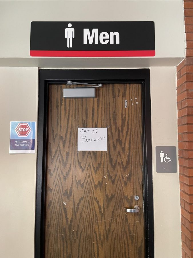 The East 100s men's bathroom with a closed sign posted on the door.