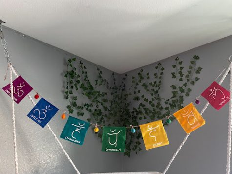 Chakra banner hanging over a hanging chair, representing the 7 main energy centers of the body.